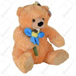 Ursulet realizat din plus tinand in mana o floare albastra