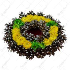 Coroana realizata din conuri de brad decorata cu flori de paie