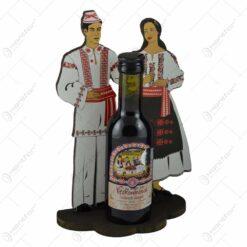 Suport sticla de vin din lemn cu silueta unei perechi in port romanesc. cu sticla de vin